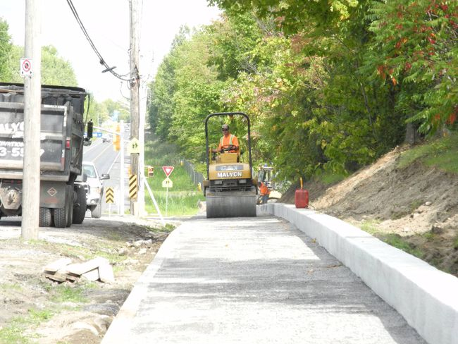 A packing machine levels the gravel on Thursday for a new sidewalk being built on the south side of Marleau Avenue, west of Nick Kaneb Drive, to accommodate the widening of Marleau, which is also being expanded east of McConnell Street. Greg Peerenboom/Cornwall Standard-Freeholder