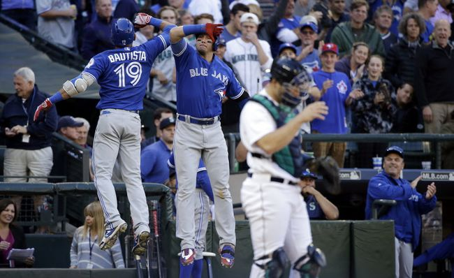 Toronto Blue Jays' Jose Bautista is congratulated by Troy Tulowitzki as Seattle Mariners catcher Jesus Sucre looks away after Bautista's home run in the ninth inning of a baseball game Wednesday, Sept. 21, 2016, in Seattle. (AP Photo/Elaine Thompson)