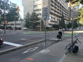 A cyclist stops at Laurier Avenue and Bay Street where the stop lines for vehicles have been moved back and for cyclists ahead, increasing the distance between the two to five metres (Susana Mas, Postmedia)