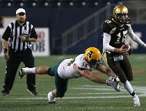 University of Manitoba Bisons QB Theo Deezar (right) avoids a tackle attempt from University of Alberta Golden Bears DL Garrett Meek during Canada West football action in Winnipeg on Fri., Sept. 16, 2016.