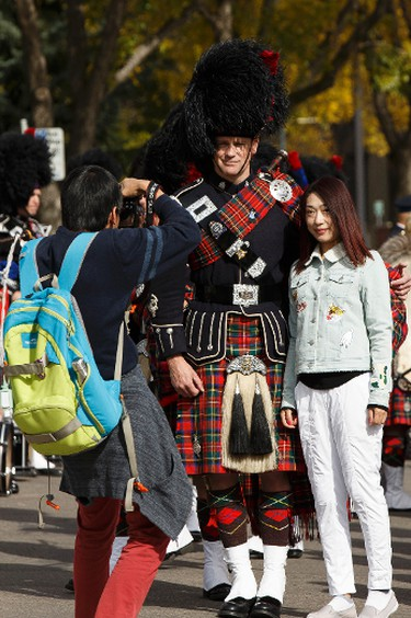 A woman gets her photo taken with a member of the Edmonton Police Service Pipes and Drums during Alberta's Police and Peace Officers' Memorial Day at the Alberta Legislature in Edmonton, Alberta on Sunday, September 25, 2016. Ian Kucerak / Postmedia