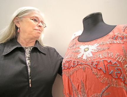Stratford Perth Museum manager of collections and exhibits Micaela Fitzsimmons shows off a beaded crepe dress typical of the early 1900s. The museum is launching a new lecture series next month examining the effect of textiles and fabrics on the development of western society. (Mike Beitz/Stratford Beacon Herald/Postmedia Network)