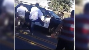 A police car, with the officer inside, was attacked by an angry mob in Fresno, Calif., Sunday. (YouTube screen grab)