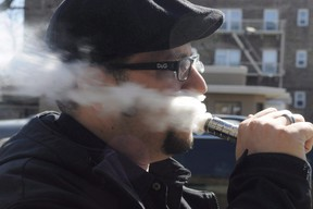 A man vapes outside a store selling electronic cigarettes and supplies Thursday April 24, 2014 in North Arliington, N.J. The Liberal government says it plans to introduce legislation later this fall to regulate vaping. (THE CANADIAN PRESS/AP Photo/Northjersey.com, Carmine Galasso)