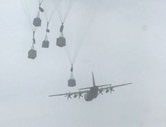 ERNST KUGLIN/THE INTELLIGENCER A Royal Australian Air Force C-130J Hercules load of containers parachutes to the ground during Exercise Bullseye held Friday at Mountainview. The Commonwealth Tactical Air Training exercise tests the skills of Austrailian, British and Canadian and C-130 Hercules pilots, aircrew and maintainers.