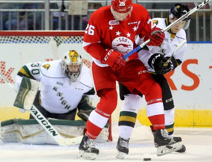 Soo Greyhounds forward Tim Gettinger (26) and London Knights defenceman Evan Bouchard fight for puck possession in front of London goaltender Emanuel Vella during first-period OHL action Friday evening in London, Ont. Mike Hensen/Postmedia Network