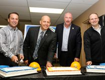 Warren Schnoor, owner of Co-operators/Advantage Insurance Group, Todd Simenson, Regional Leader - Alberta North and Territories for Stantec, City of Lacombe Mayor Steve Christie, and Scott Builders Inc. Operations Manager Mike Wagner (left to right) cut a trio of cakes in celebration of becoming sponsors for the Gary Moe Auto Group Sportsplex dressing rooms and concession, respectively, from inside the Freightliner of Red Deer Curling Complex last Wednesday afternoon. (Ashli Barrett, Lacombe Globe)