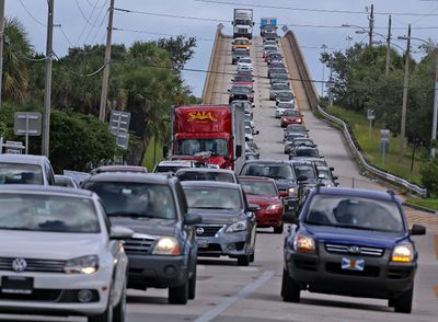 People in vehicles make an evacuation route over 520 bridge heading west from Merritt Island, Fla., Wednesday, Oct. 5, 2016, as Hurricane Matthew approaches Florida. (Red Huber/Orlando Sentinel via AP)