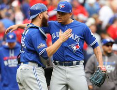 Russell Martin and Roberto Osuna celebrate as the Jays hung on to beat Texas 5-3 in Game 2 of the ALDS on Friday. (Getty Images)