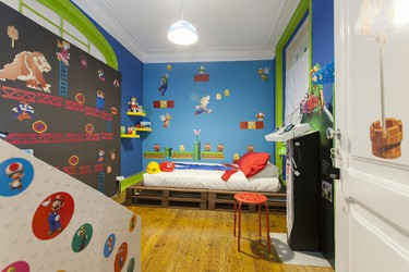 """Based in Lisbon, Portugal, Airbnb host Andre Farinha has created a Nintendo-lover's paradise in the apartment's bedroom and bathroom, which pay homage to Super Mario's thirty-year history. Gaming enthusiasts will be happy to learn that the main room features a Wii U, a display of amiibo characters, and a Nintendo 3DS stand where guests can play The Legend of Zelda: Ocarina of Time. Farinha, a 32-year-old computer game programmer and self-described """"major nerd,"""" spent more than US$11,000 designing the space, but paying guests need only part with $39 a night! (Airbnb/WENN.com)"""