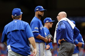 Toronto Blue Jays manager John Gibbons checks on relief pitcher Francisco Liriano after Liriano was hit on the back of the head by a single off the bat of Texas Rangers' Carlos Gomez in the eighth inning of Game 2 of an American League Division Series on Oct. 7, 2016, in Arlington, Texas. (AP Photo/LM Otero)