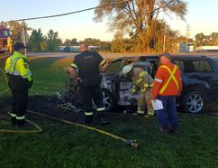 An SUV driver is tended by Brant County OPP and paramedics after a crash with a tractor trailer at Oak Park Road and Powerline Road on Monday at about 5:30 p.m. (David Ritchie)