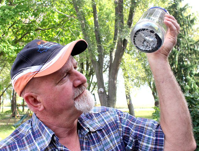 Marc St. Pierre looks at the sediment that is in the unfiltered water coming from the water well at his home on Bay Line near in Mitchell's Bay, Ont. on Tuesday October 11, 2016. (Ellwood Shreve/Chatham Daily News)