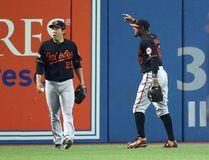 Hyun Soo Kim #25 of the Baltimore Orioles and Adam Jones #10 react in the seventh inning after a fan threw a beverage onto the field during the American League Wild Card game against the Toronto Blue Jays at Rogers Centre on October 4, 2016 in Toronto, Canada. (Photo by Tom Szczerbowski/Getty Images)