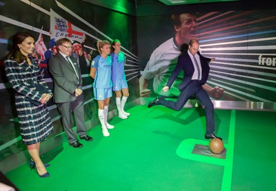 Britain's Prince William kicks a football in the simulator, watched by Kate Duchess of Cambridge, Friday Oct. 14, 2016, at The national football museum, in Manchester, England. The royal couple are visiting Manchester for a day of engagements. (Charlotte Graham/Pool via AP)
