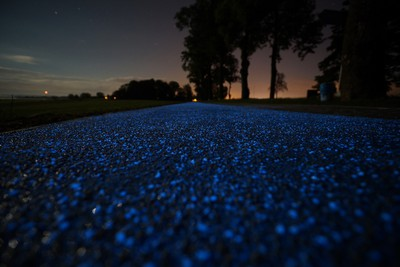 "This luminous blue cycling lane, which can be found near Lidzbark, Warminski in the north of Poland is the brainchild of TPA laboratory in Pruszkow. Built by the STRABAG company, the path was created using a synthetic material that is charged during the daylight hours and can give off light for up to 10 hours during the night. The surface of the luminous path contains so called luminophores. These special inorganic substances ""charge"" when exposed to the sunlight and later emit accumulated energy. (Supplied by WENN.com)"