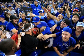 Marco Estrada of the Toronto Blue Jays is swarmed by fans after the Blue Jays defeated the Texas Rangers in Game 3 of the American League Division Series at Rogers Centre on Oct. 9, 2016 in Toronto. (Vaughn Ridley/Getty Images)