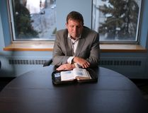 Jason Caldwell, father of twins Jordan and Evan Caldwell, looks through Jordan's bible in his Calgary office. Jason is will be speaking at this year's Calgary Prayer Breakfast about how his faith has helped him and his family deal with the tragic loss of the two young men in a tobogganing accident at Canada Olympic Park last February. Jordan hand wrote many notes in the margins of the bible that family members love to read. Photo by Gavin Young/Postmedia