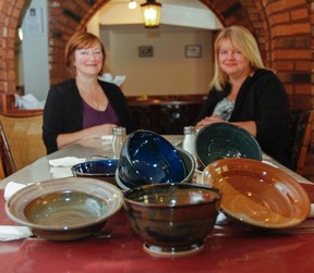 Ronda Candy, left, executive director of Martha's Table, and Tina Malm, administrator, are putting the finishing touches on the Empty Bowls fundraiser, which will take place Oct. 23. (Julia McKay/The Whig-Standard)