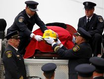 Emily Mountney-Lessard/The Intelligencer The helmet of Quinte West firefighter Jason Forth is lowered from the back of a fire truck just before Forth's celebration of life at Trenton United Church, Monday October 17, 2016 in Trenton, Ont. Forth, 43, died on Oct. 11 after a long battle with cancer. He was a full-time firefighter with Station 1 in Trenton.