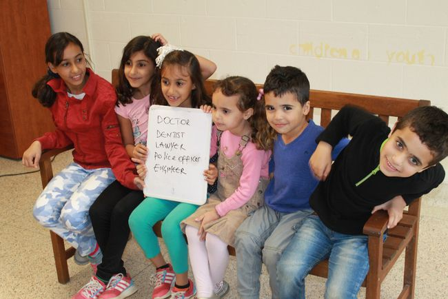 A group of young newcomers sit on a bench, holding a list of careers they intend to pursue. From left to right: Rooa Al-Khalil, 10, Raghd Al-Khalil, 9, Rahaf Al-Khalil, 7, Nour Almudeer, 5, Mohammad Almudeer, 5, Odai Almudeer, 7. 