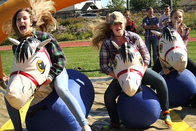 Tory Arnold, left, Britney Nutt, and Grace Renner at the inflatable horse races activity on Ag Day.