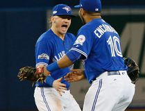 Blue Jays' Josh Donaldson (left) and Edwin Encarnacion (right) react after defeating the Indians in Game 4 of the AL Championship Series in Toronto on Tuesday, Oct. 18, 2016. (Stan Behal/Toronto Sun)