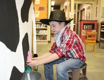 """Young cowboys and cowgirls had an opportunity to """"milk a cow"""" at the Melfort library on October 19."""