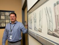 Dr. Charles Nelson, the psychologist in charge of the Operational Stress Injury Program at Parkwood Hospital, stands beside a piece of art depicting footwear worn by soldiers and RCMP officers - the clinic's patients are made up of RCMP and military personnel - in the reception area of the program at Parkwood Hospital in London, Ont. on Thursday October 20, 2016. Craig Glover/The London Free Press/Postmedia Network