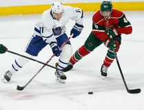 Maple Leafs' Zach Hyman controls the puck through the defence of the Wild's Jason Pominville (left) and Jared Spurgeon (right) during first period NHL action in St. Paul, Minn., on Thursday, Oct. 20, 2016. (Stacy Bengs/AP Photo)