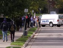A police van patrols on Broughdale Avenue as a small group of homecoming revellers gathers on the largely student-populated street that has become synonymous with large parties on homecoming weekends in years past. Craig Glover/The London Free Press/Postmedia