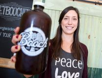 Shannon Slade, co-owner of Booch Organic Kombucha, holds up a bottle filled with Concord grape anise flavoured kombucha at the Dundas Street store operated by her and her husband, Shawn. No machines are used to brew the beverage, which takes two weeks to make. (CRAIG GLOVER, The London Free Press)