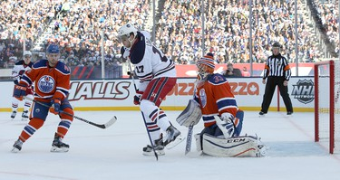 WINNIPEG, MANITOBA - OCTOBER 23: Adam Lowry #17 of the Winnipeg Jets tries to deflect a shot past Cam Talbot #33 of the Edmonton Oilers during the 2016 Tim Hortons NHL Heritage Classic hockey game on October 23, 2016 at Investors Group Field in Winnipeg, Manitoba, Canada. (Photo by Jason Halstead /Getty Images)