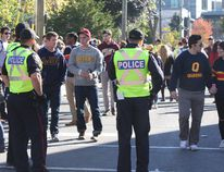 Kingston Police officers monitor the crowd on Aberdeen Street on Oct. 15 during Homecoming weekend at Queen's University. (Steph Crosier/The Whig-Standard)