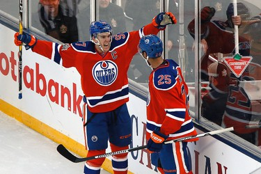 Edmonton Oilers' Darnell Nurse (25) and Connor McDavid (97) celebrate Nurse's goal against the Winnipeg Jets during second period NHL Heritage Classic action in Winnipeg on Sunday, October 23, 2016. THE CANADIAN PRESS/John Woods ORG XMIT: JGW120