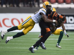 Deon Lacey tackles Lions slotback Manny Arecenaux during Saturday's game in Vancouver. (The Canadian Press)