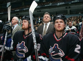 From left, Henrik Sedin, head coach Marc Crawford and Daniel Sedin look on from the Canucks bench during the 2005 season. Crawford is back in Vancouver as an associate coach with the Senators to face the Canucks tonight. (Getty Images)