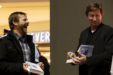 Allan Peters (left) tells a joke about the Titanic and the Calgary Flames as he meets Edmonton Oilers great Wayne Gretzky at a book signing at West Edmonton Mall in Edmonton, Alberta on Monday, October 24, 2016. Ian Kucerak / Postmedia