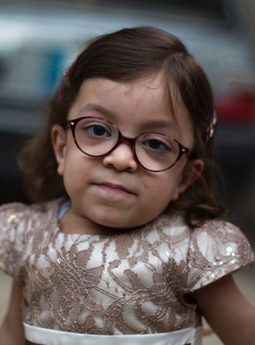 In this Thursday, Oct. 20, 2016 photo, Maria, who is suffering from a disease known as Morquio Syndrome, poses for a picture in Rawalpindi, Pakistan. The U.S. embassy in Islamabad issued a last minute visa to Maria, an ailing 6-year-old Pakistani child, afflicted with a painful genetic disorder, and her parents who turned to the media as the date for their child's life altering operation in the United States loomed. (AP Photo/B.K. Bangash)