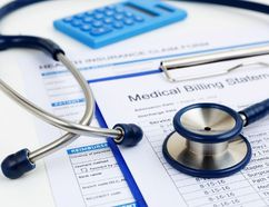 Stethoscope on medical bills and health insurance claim form. (Getty Images/iStockphoto)