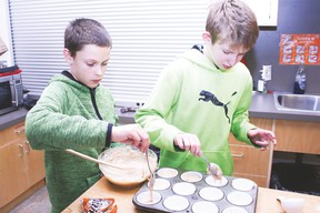 Grade 6 students Logan Gorzitza and Connor Mitchell fill a baking sheet with banana muffin batter during the Vulcan Volunteer program Friday afternoon at the Vulcan Prairieview Elementary School.