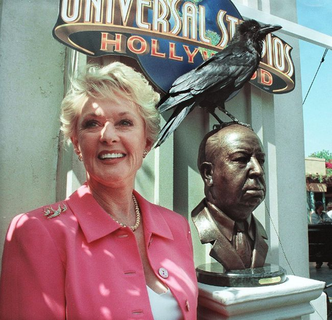 Former actress Tippi Hedren stands next to the unveiled bronze bust of the late director Alfred Hitchcock during a June 27, 1999 ceremony at Universal Studios in Los Angeles, California. (SCOTT NELSON/AFP/Getty Images)