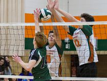 Brian Coon (foreground) of St. John's attempts to tip the ball past North Park defenders Matt Bell (centre) and Cal Hager during a high school senior boys sudden-death semifinal volleyball match on Tuesday. (Brian Thompson/The Expositor)
