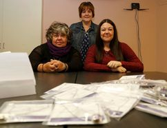 Emily Mountney-Lessard/The Intelligencer Sandy Watson-Moyles, Jennifer Loner and Leah Morgan, all from Three Oaks, pose for a photo at the shelter in Belleville on Thursday. In front are packages of Sugar Snap necklaces, which will be offered for sale later this month as one of their Domestic Violence Awareness Month fundraisers.