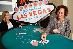 Luke Hendry/The Intelligencer The United Way's Lyndsey Harker, left, and Judi Gilbert demonstrate blackjack Thursday at their office in Belleville. About 15 tables will be part of the entertainment at the United Way's Viva Las Vegas Charity Casino Saturday at Trenton's National Air Force Museum of Canada.