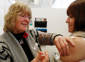 Luke Hendry/The Intelligencer Registered nurse Lois Farnell-Woodman injects Quinte Health Care medical/critical care program director Christine Wilkinson with influenza vaccine at Belleville General Hospital Monday. Staff vaccinations have increased compared to those of last fall.