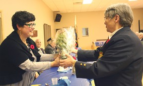 The branch service officer from the Seaforth Legion, Lin Steffler presents flowers to Major George Garrard's wife last Saturday.(Shaun Gregory/Huron Expositor)
