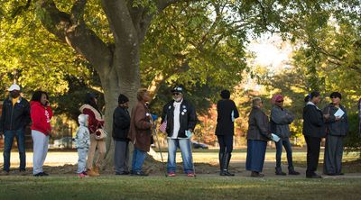 Spellman Bernard Smith, Jr. ,78, center, stands in line with other voters at Rosemont Middle School in Norfolk, Va., on Election Day, Tuesday morning, Nov. 8, 2016 to cast his vote. Smith, a felon, recently had his voting rights restored and he was able to cast a vote for president for the first time. (Bill Tiernan/The Virginian-Pilot via AP)