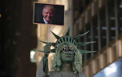 A street performer dressed as the Statue of Liberty holds a picture of U.S. President-elect Donald Trump in Hong Kong's downtown, Wednesday, Nov. 9, 2016. (AP Photo/Kin Cheung)