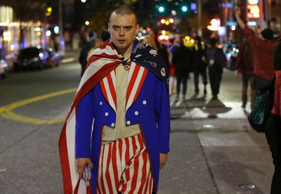 A man wearing red-white-and-blue takes part in a protest against President-elect Donald Trump, early Wednesday, Nov. 9, 2016, in Seattle's Capitol Hill neighborhood. (AP Photo/Ted S. Warren)